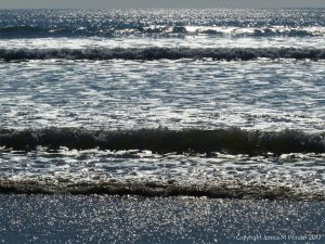 Waves and surf on the incoming tide sparkling in the sunshine