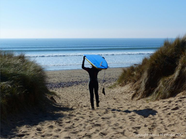 Young surfer emerging from the dunes at Rhossili beach in Gower