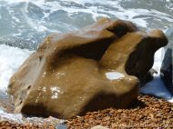 Strange shaped boulder splashed by waves on the pebble beach at Seatown in Dorset