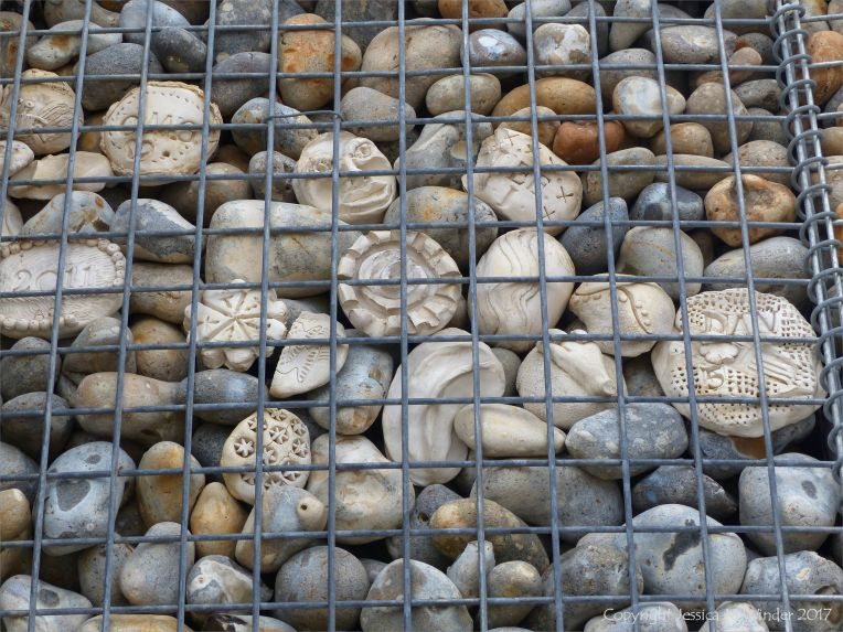Natural pebbles and decorative hand-made ceramic pebbles in wire cages called gabions