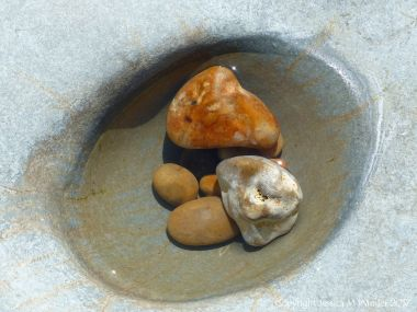 Pebbles in a water-filled smooth rock hollow