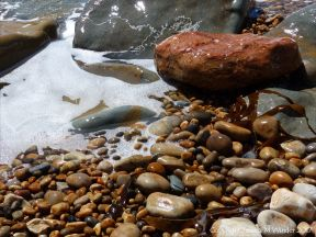 Colourful wet pebbles in the breaking waves at the waters' edge on the beach