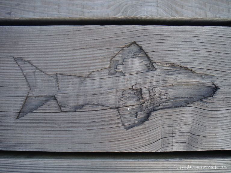 Fish carving in a wooden plank on a pier
