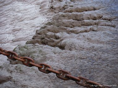 Rusty mooring chain and muddy river bank