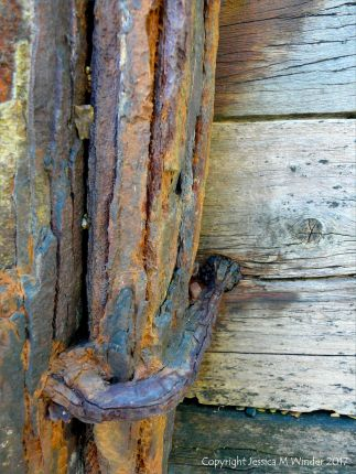 Rusty iron upright on an old wooden breakwater