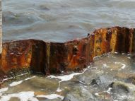 Rusting ironwork support from a delapidated breakwater
