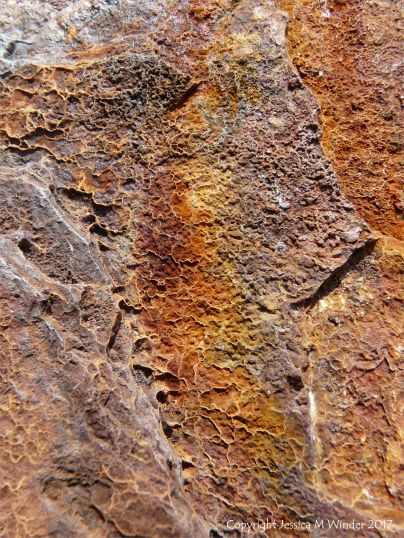 Close-up of texture in rust on an old iron support for a breakwater on the beach