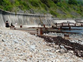 Wooden breakwaters with rusty iron fittings on the seashore