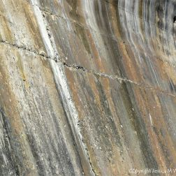 Natural pattern of stripes on an old concrete sea wall