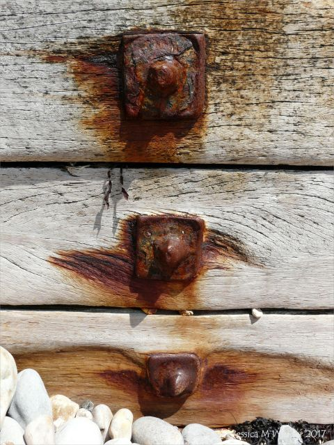 Rusty iron fitments on a wooden breakwater on the seashore