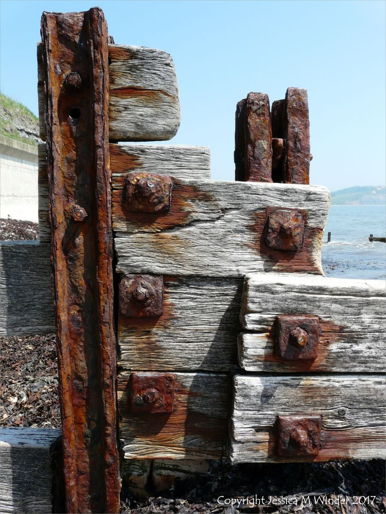 Rusting ironwork on a wooden breakwater