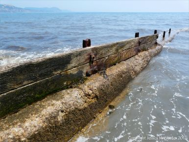 Old breakwater or groyne projecting into the waves