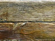 Curvilinear etched woodgrain patterns in weathered timber on a seashore breakwater