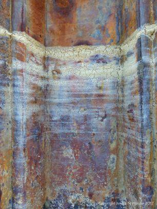 Pattern of dried sea foam tide lines on a rusty iron pier