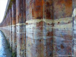 Looking seawards along the iron pier work showing sea foam tide lines