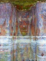 Lines of dried sea foam on a rusty iron pier