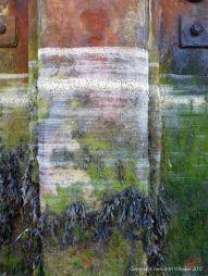 Lines of dried sea foam left by the receeding tide on a rusty pier