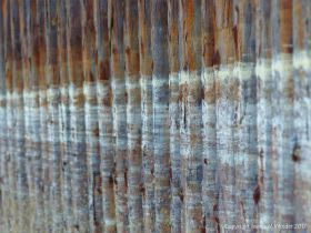 Tide marks or tide lines of dried sea foam on the vertical rusty iron surfaces of pier supports.