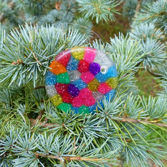 Colourful lost plastic button lodged in a pine tree at Kew Gardens