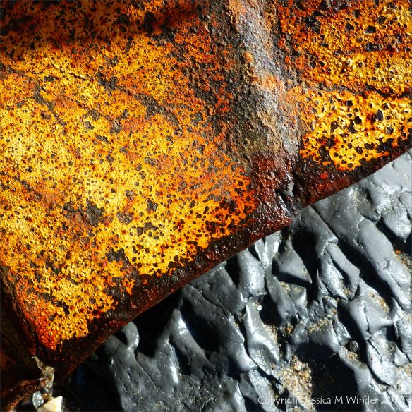 Rusty painted metal junk on the seashore with rocks