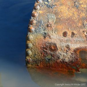 Rusty metal object in a tide pool on the beach