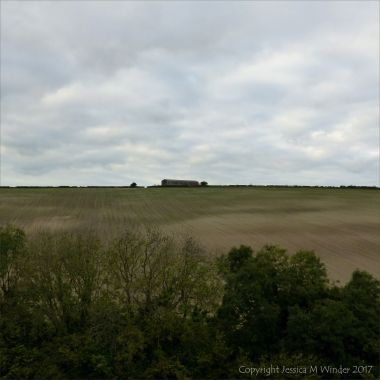 Farming landscape in the Dorset countryside with arable field, barn, and hedgerow