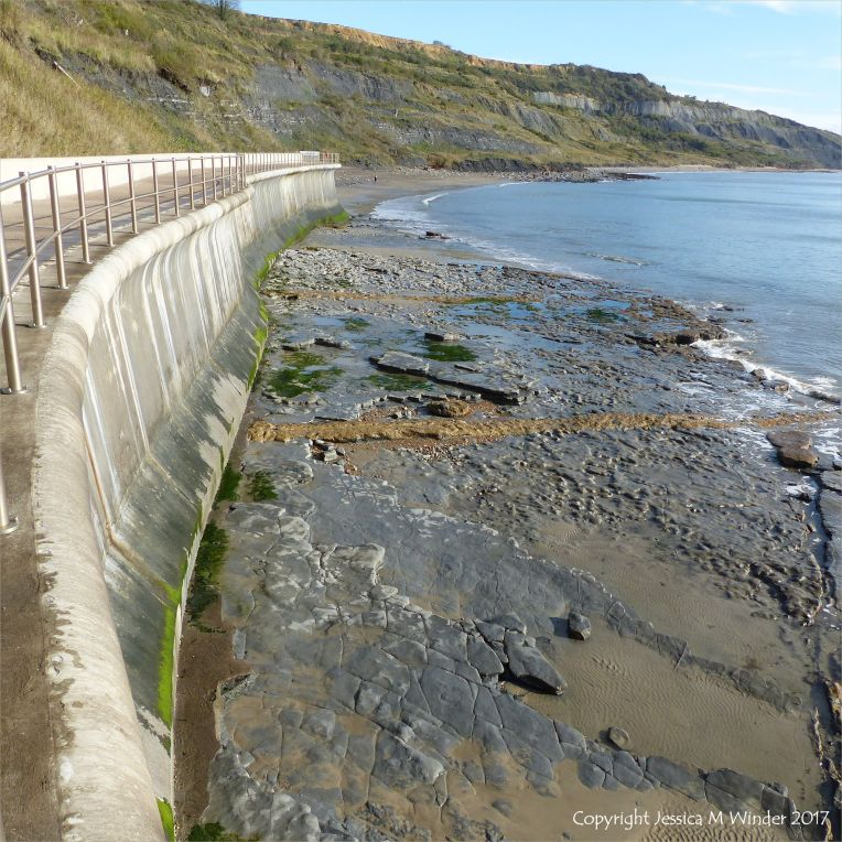 View looking east from the new sea wall at Lyme Regis showing bare rock platform on beach with concrete lines of old footings from the demolished breakwaters.