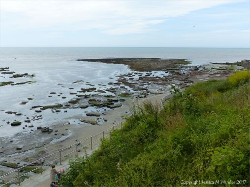 View looking down on the rocky shore below the new sea wall at Lyme Regis