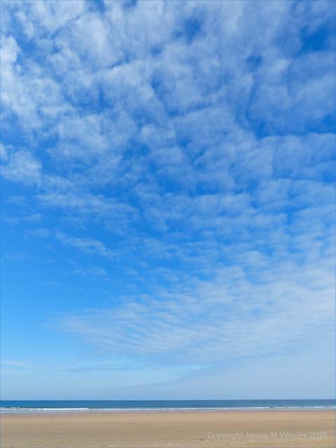 Rhossili Beach on a summer day showing big blue sky