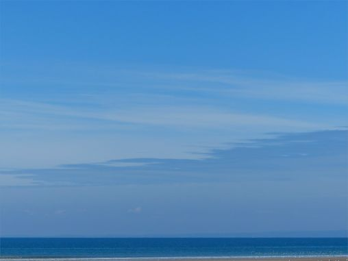 Rhossili Beach on a summer day showing big blue sky