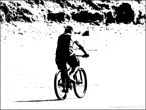 Black and white image of a man cycling across a beach