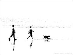 Black and white image of people walking their dog on the water's edge at the beach