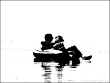 Black and white image of a man and his dog chilling out in an inflatable on the beach