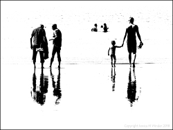 Black and white image of people on the water's edge at the beach