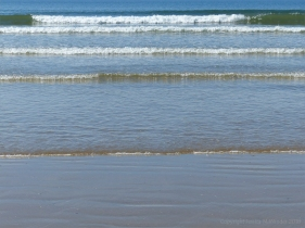 Rhossili Beach on a summer day showing waves lapping onto the shore