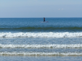 Rhossili Beach on a summer day showing blue sea, surf, and paddle boarder