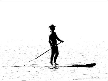 Black and white image of a paddle boarder