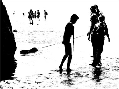 Black and white image of people with a dog in a tide pool