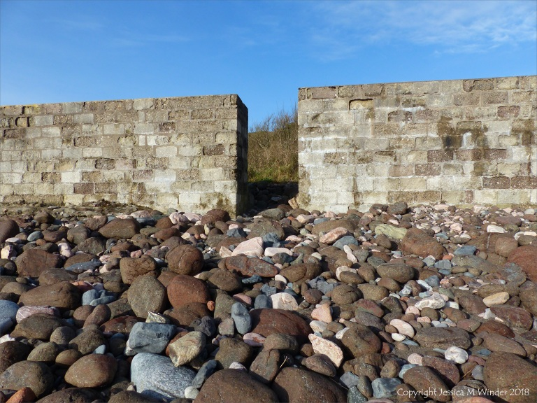 Sea wall and beach boulders at Kennack Sands