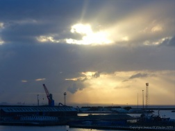 Early light breaking through winter clouds over docks with cranes