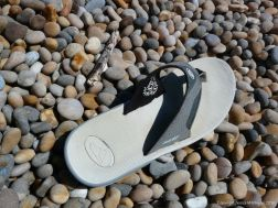 Flip-flop sandal washed up on a pebble beach