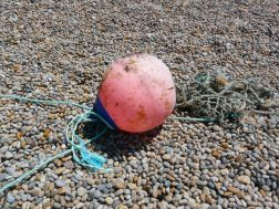 Red buoy washed up on a pebble beach