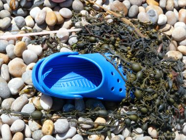 Blue Croc shoe and seaweed washed up on a pebble beach