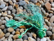 Green knotted rope washed up on a pebble beach