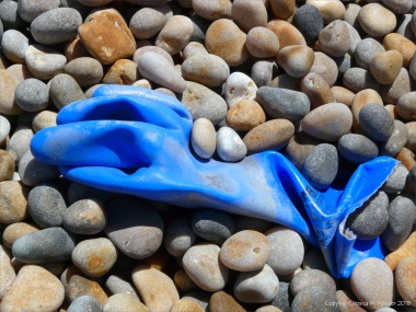 Blue plastic glove washed up on a pebble beach