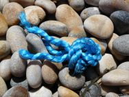 Piece of blue knotted rope washed up on a pebble beach
