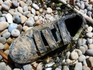 Black shoe with hydroid encrustation washed up on a pebble beach