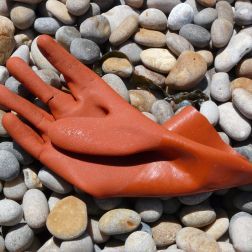 Orange plastic glove washed up on a pebble beach