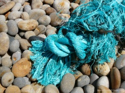 Piece of green knotted rope washed up on a pebble beach