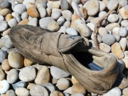 Old shoe washed up on a pebble shore